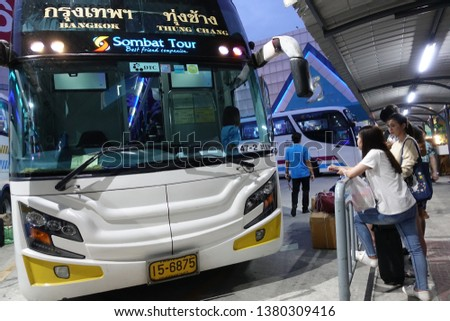 """Bangkok-Thailand:April 7,2019:People wait for buses inside bus terminal for long holiday, Songkran Festival. they carry passenger's goods and luggage.This bus terminal calls """"Sombattour"""" in night time #1380309416"""