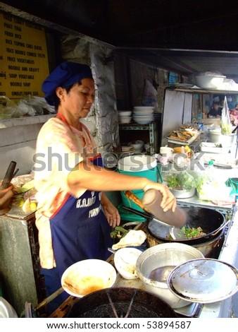 BANGKOK, THAILAND - APRIL 3: Thai woman cooks food in an outdoor kitchen April 3, 2007 in Bangkok.