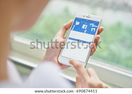 Bangkok, Thailand - August 06, 2017 : hand is pressing the Facebook screen on apple iphone6 ,Social media are using for information sharing and networking.