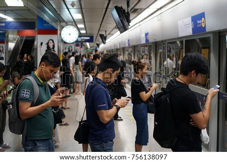 Bangkok Thailand - August 20, 2017: The passengers line up to waiting for MRT subway train and using smartphones to kill time in rush hour, Mobile phone addiction lifestyle daily, Social technology