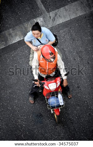 BANGKOK, THAILAND - CIRCA DECEMBER 2008: An unidentified woman catches a ride on one of the many motorcycle taxi's in the busy city CIRCA DECEMBER 2008.