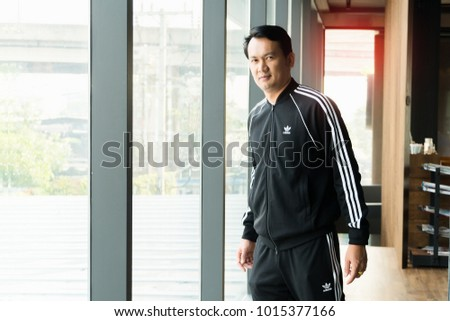 BANGKOK, THAILAND - DECEMBER 21, 2018 :A man wearing new collction adidas original jacket and sweatpants,  A German multinational corporation that designs and manufactures sports shoes, clothing  #1015377166