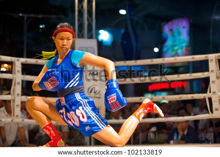 BANGKOK, THAILAND - DECEMBER 8, 2010: An unidentified female muay thai kickboxer performs a kicking routine in a kickboxing ritual called the wai khru on December 8, 2010 in Bangkok, Thailand