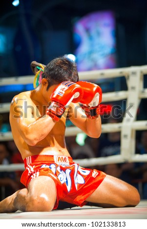 BANGKOK, THAILAND - DECEMBER 8, 2010: An unidentified muay thai kickboxer kneels and prays with his gloves during a pre-fight ritual called the wai khru on December 8, 2010 in Bangkok, Thailand