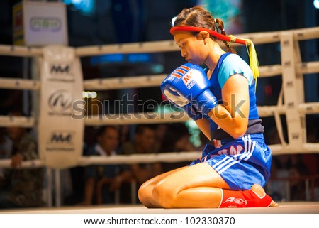 Bangkok, Thailand - December 8, 2010: Female muay thai fighter kneeling, gloves raised, seemingly reflecting in a kickboxing ritual called the wai khru meant to honor her teachers at amateur match
