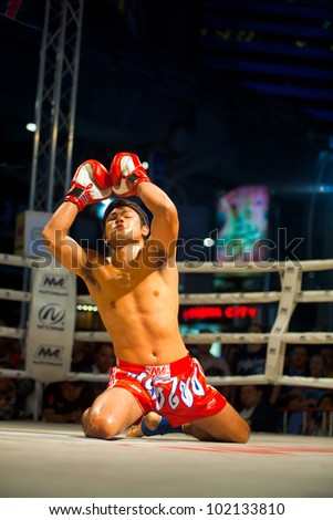 Bangkok, Thailand - December 8, 2010: Kneeling male muay thai kickboxer in red trunks raising his arms, looking up and chanting during a traditional kickboxing ritual called the wai khru before fight