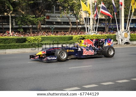 stock photo : BANGKOK,THAILAND - DECEMBER 18: Mark Webber of Red Bull Racing Team speeding shows on Street of Kings, Ratchadamnoen Red Bull Bangkok 2010. December 18, 2010 in Bangkok,Thailand