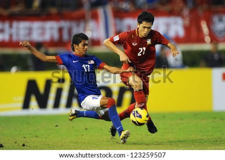 BANGKOK THAILAND-DECEMBER 13:Piyapol Bantao #21 of Thailand (red) run with the ball during the AFF Suzuki Cup between Malaysia and Thailand at Supachalasai stadium on Dec13,2012 in Bangkok,Thailand.