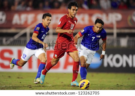 BANGKOK THAILAND-DECEMBER 13:Teerasil Dangda of Thailand (red) run with the ball during the AFF Suzuki Cup between Malaysia and Thailand at Supachalasai stadium on Dec13,2012 in ,Thailand.