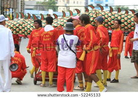 BANGKOK, THAILAND - DECEMBER 23 : Thai people dressed in red and white parade down a road in Bangkok suburbs in preparation for Chinese New Year. December 23 2009 in Bangkok.