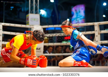 BANGKOK, THAILAND - DECEMBER 8, 2010: Two unidentified female muay thai fighters side by side perform a kickboxing ritual called the wai khru on December 8, 2010 in Bangkok, Thailand