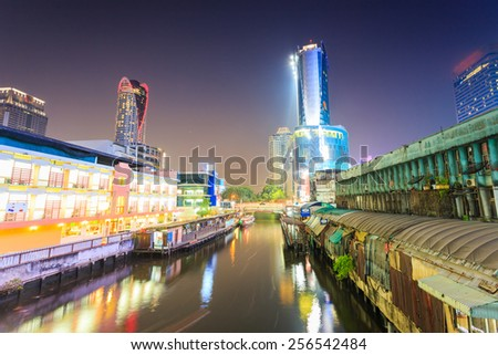 Bangkok, Thailand - February 8, 2015: Skyscraper and Pratunam pier in Bangkok; water transportation by speed boat is one of the alternative choice for solving the traffic congestion problem in Bangkok