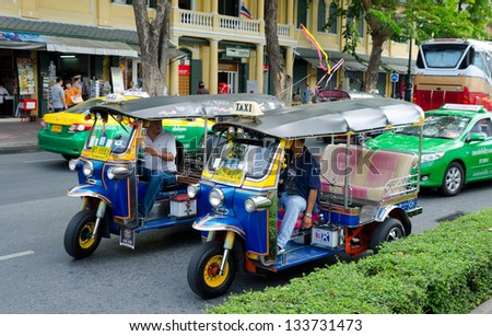 BANGKOK, THAILAND - FEBRUARY 18: Unidentified motorbike taxi drivers talk to each other moving along a street, Feb 18, 2013, Bangkok, Thailand. Such motorbike taxis are called tuktuks in Thailand.