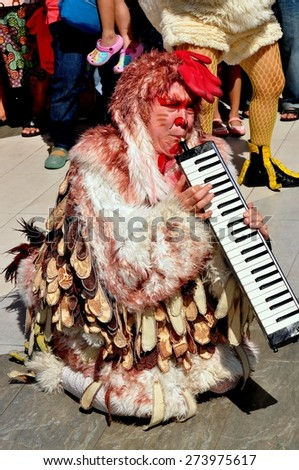 Bangkok, Thailand - January 11, 2013:  Musician in a chicken costume entertains crowds at the Children\'s Day festivities in the Siam Paragon shopping center outdoor plaza