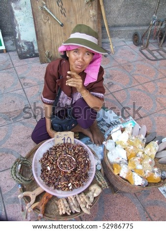 BANGKOK, THAILAND - JANUARY 20 : Thai woman sells roasted nuts by the road January 20, 2006 in Bangkok.