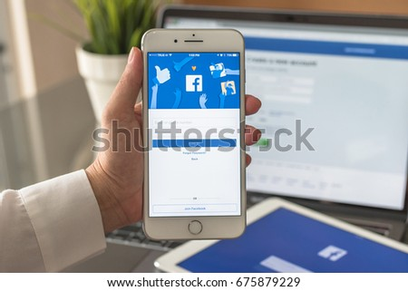 BANGKOK, THAILAND - July 10, 2017: Facebook social media app logo on log-in, sign-up page on mobile app screen on iPhone smart devices in business person's hand