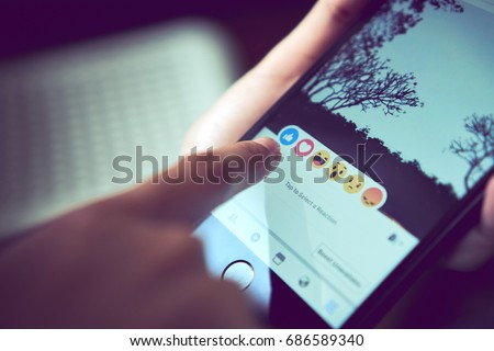 Bangkok, Thailand - July 30, 2017 : hand is pressing the Facebook screen on apple iphone6 ,Social media are using for information sharing and networking.