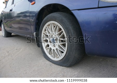 BANGKOK Thailand-JUNE 24, 2018 :Closeup for car wheel flat tire on the road .                                                          #1119999038