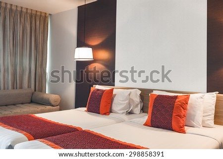 BANGKOK THAILAND - JUNE 18 : Red pillow on double bedroom with white bed sheet and lamp light on, in Spring Field at Sea hotel in Cha-am Phetchaburi, Thailand on June 18, 2015
