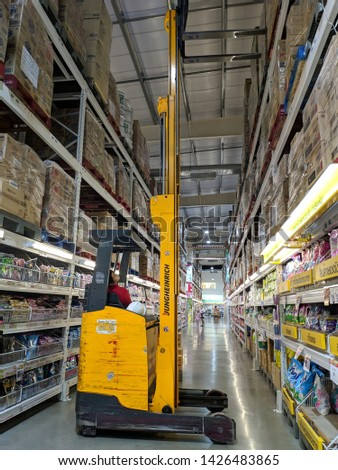 Bangkok, Thailand -June 15, 2019 : Warehouse loader forklift lifting pallet with big box package at store warehouse. Worker relocating goods in warehouse area. #1426483865