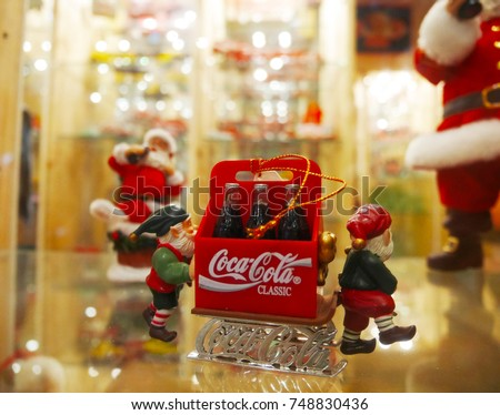 BANGKOK, THAILAND - MARCH 25, 2017: Little Gnomes dragging a cart full of bottles of Coca Cola, Christmas Concept #748830436