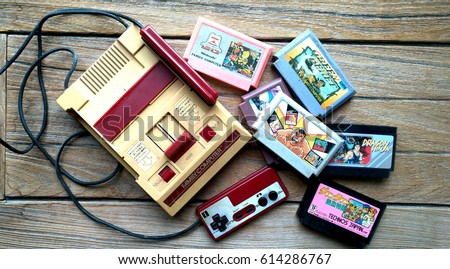 BANGKOK, THAILAND - MARCH 31, 2017 : Old Nintendo Entertainment System Family Computer and game cartridges on wooden background. Illustrative editorial