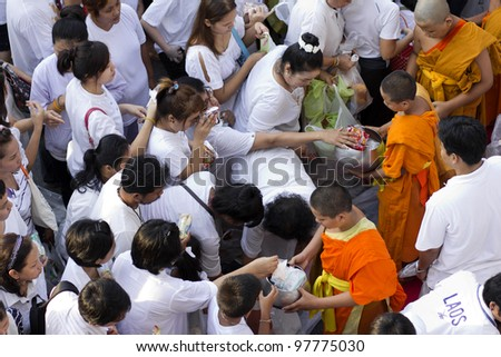BANGKOK , THAILAND - MARCH 17: People give food offerings to a Buddhist monk on March 17, 2012 in Bangkok, Thailand. Thai traditional, people will make merit making by give food to monk