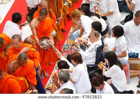 BANGKOK , THAILAND - MARCH 18: People Gives food offerings to a Buddhist monk on March 18, 2012 in Bangkok, Thailand. Thai traditional, people will make merit making by give food to monk