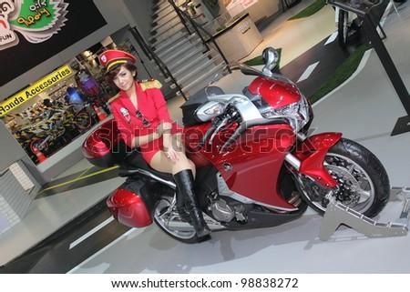 BANGKOK, THAILAND- MARCH 29: Unidentified female presenters with Honda  motorcycle  on display at  the Bangkok International Motorshow 2012 on March 29, 2012 in Bangkok,Thailand