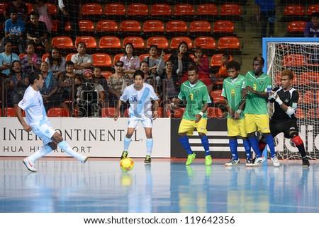 BANGKOK,THAILAND-NO VEMBER 09:Alan Aguilar #11 of Guatemala (L) shoot the ball during the FIFA Futsal World Cup between Solomon Islands and Guatemala at Indoor Stadium Huamark on Nov9,2012 in,Thailand. - stock photo