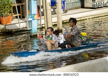 BANGKOK, THAILAND - NOV 12: Family transporting by taxi boat after the city was flooded on November 12, 2011 in Bangkok, Thailand.