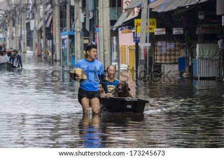BANGKOK, THAILAND - NOV 5, 2011: People and dogs with their transportation during a big flooding in Thailand. At Phongphet junction, Ngamwongwan road.