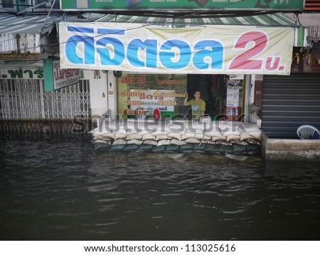 BANGKOK, THAILAND - NOV 17 - Thai flood hits Central of Thailand, overflow water while people use sand bag to protect house - at Pahonyothin road on November 17, 2011 in Bangkok, Thailand