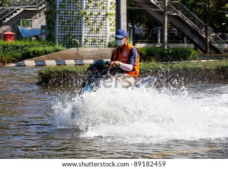 BANGKOK, THAILAND - NOVEMBER 12 : A man on a motorbike navigating through the flood after the heaviest monsoon rain in 20 years in the capital on November 12,2011 Bangkok, Thailand.