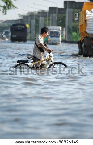 BANGKOK, THAILAND - NOVEMBER 04: An unidentified man holding a bicycle through the flood in Bangkok on November 04, 2011 in Bangkok, Thailand.