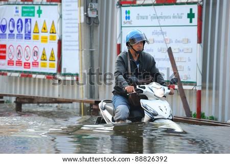 BANGKOK, THAILAND - NOVEMBER 04: An unidentified man riding motorcycle wade through flood in Bangkok on November 04, 2011 in Bangkok, Thailand.