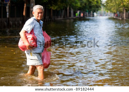 BANGKOK, THAILAND - NOVEMBER 12 : An unidentified man wades through a flooded Bangkok street, during the worst flooding in decades on  November 12,2011 Bangkok, Thailand.