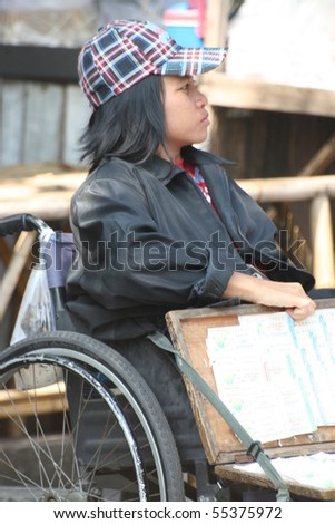 BANGKOK, THAILAND - NOVEMBER 29: Disabled lady sells lottery tickets in Chatuchak market on November 29, 2008 in Bangkok.