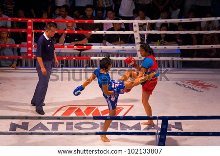 Bangkok, Thailand - November 17, 2010: Female muay thai kickboxer in blue kick jab kicking oppenent is blocked by the arm as male referee officiates at amateur outdoor kickboxing event