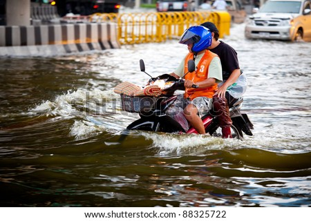 BANGKOK, THAILAND - NOVEMBER 5 : Two men on a motorbike navigating through the flood after the heaviest monsoon rain in 20 years in the capital on November 5,2011 Bangkok, Thailand.