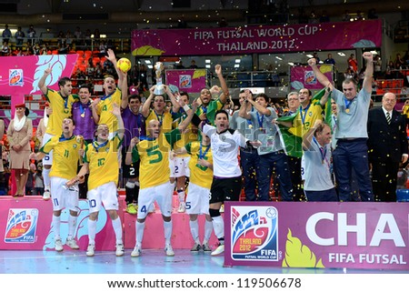 BANGKOK, THAILAND - NOVEMBER 18: Vinicius (no.7) of Brazil lifts the trophy after winning the FIFA Futsal World Cup Final at Indoor Stadium Huamark on November 18, 2012 in Bangkok, Thailand.