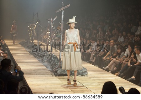 "BANGKOK, THAILAND - OCTOBER 13 : A model is walking the runway at "" 27 Friday "" collection presentation during ELLE Fashion Week 2011 Autumn/Winter on October 13, 2011 in Bangkok, Thailand."