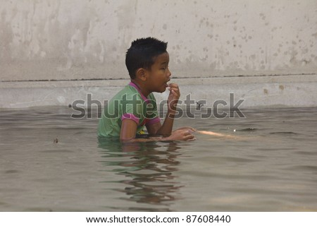 BANGKOK THAILAND - OCTOBER 27 : An unidentified boy plays in flood water on the road on October 27, 2011 at Tha Tien. Bangkok, Thailand.