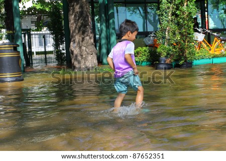 BANGKOK THAILAND - OCTOBER 29 : An unidentified boy walking in flood water from monsoon rain on the road at Sanam luang on October 29, 2011, Bangkok, Thailand. - stock photo