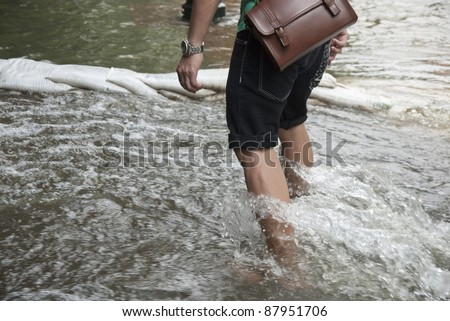 BANGKOK THAILAND - OCTOBER 31 : An unidentified man walking in flood water on the road  during flooding crisis on October 31,2011 at Tha Prachan area in Bangkok, Thailand
