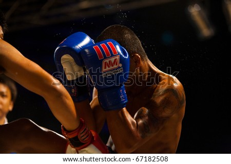 Bangkok, Thailand - October 12, 2010: Asian boxer with gloves up receiving punch to head sending sweat flying at outdoor amateur muay thai kickboxing match