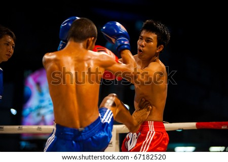 Bangkok, Thailand - October 12, 2010: Asian muay thai fighter receiving kick jab to stomach, ribs at amateur outdoor kickboxing event