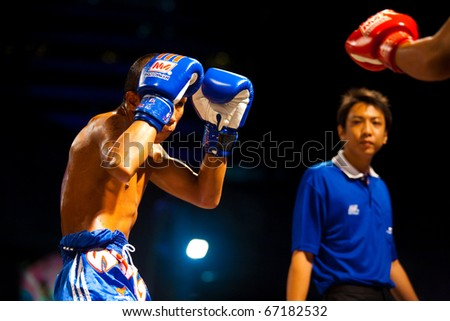 Bangkok, Thailand - October 12, 2010: Muay thai fighter raising boxing gloves up in a guarded stance with referee watching