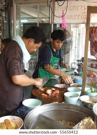 BANGKOK, THAILAND - OCTOBER 28: Thai men cook food in an outdoor kitchen  on October 28, 2005 in Bangkok.