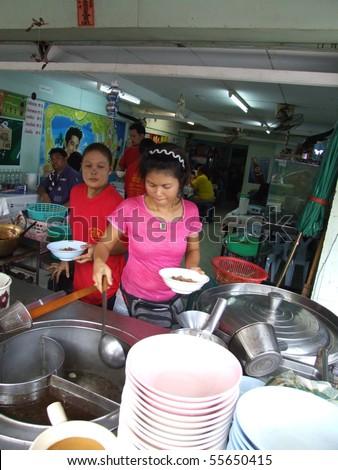 BANGKOK, THAILAND - OCTOBER 28: Thai woman cooks food in an outdoor kitchen on October 28, 2005 in Bangkok.